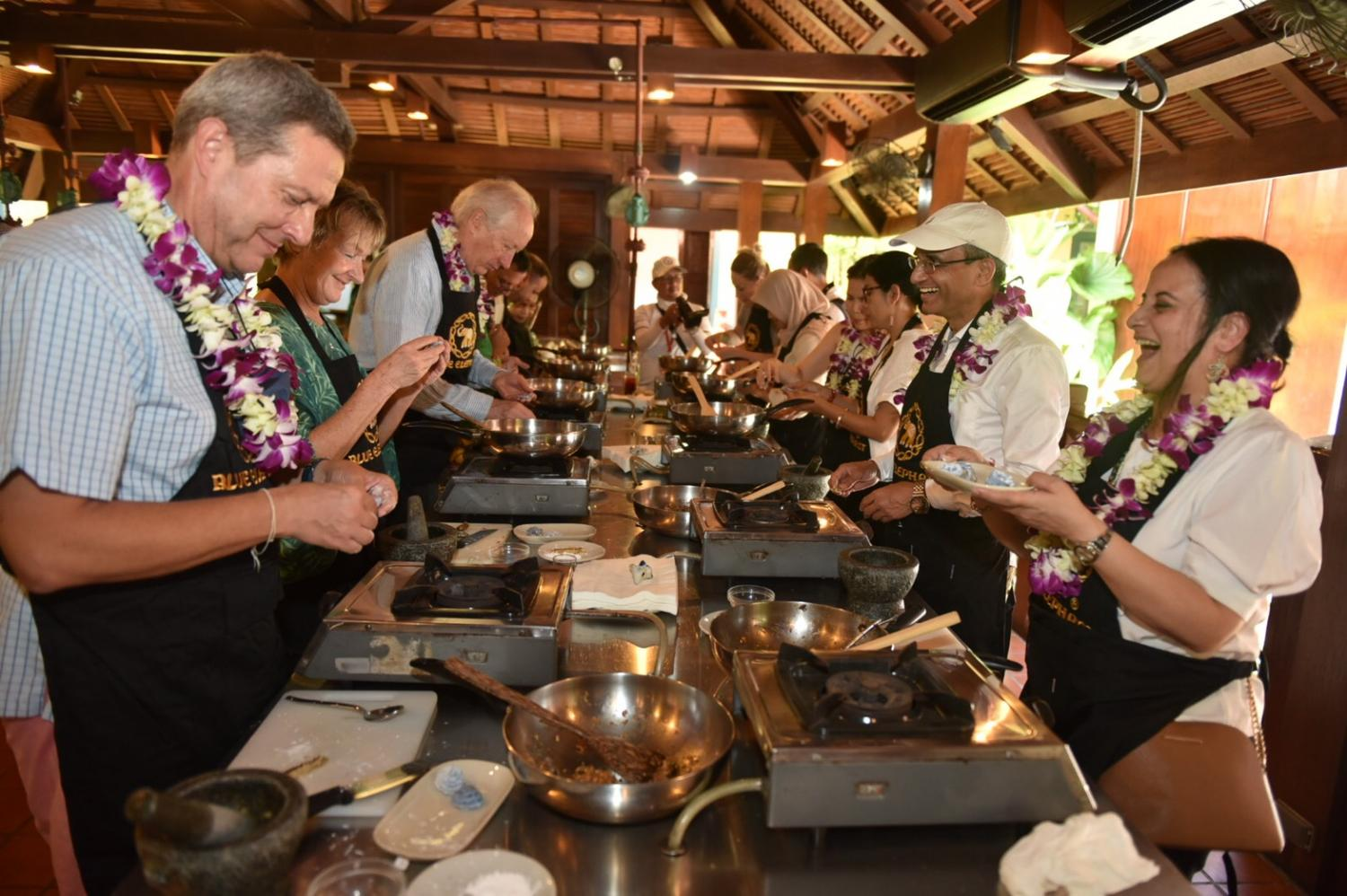 Diplomats and their spouses try their hands at cooking during a tour of  Phuket Old Town on Sunday. The envoys visited the island province in a campaign to revitalise the local tourism industry hit hard by the Covid-19 pandemic.(Photo by Achadthaya Chuenniran)