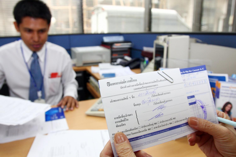 An elderly investor buys government savings bonds in the Thai Strength scheme at Bangkok Bank in 2009.(Photo by Kitja Apichonrojarek)