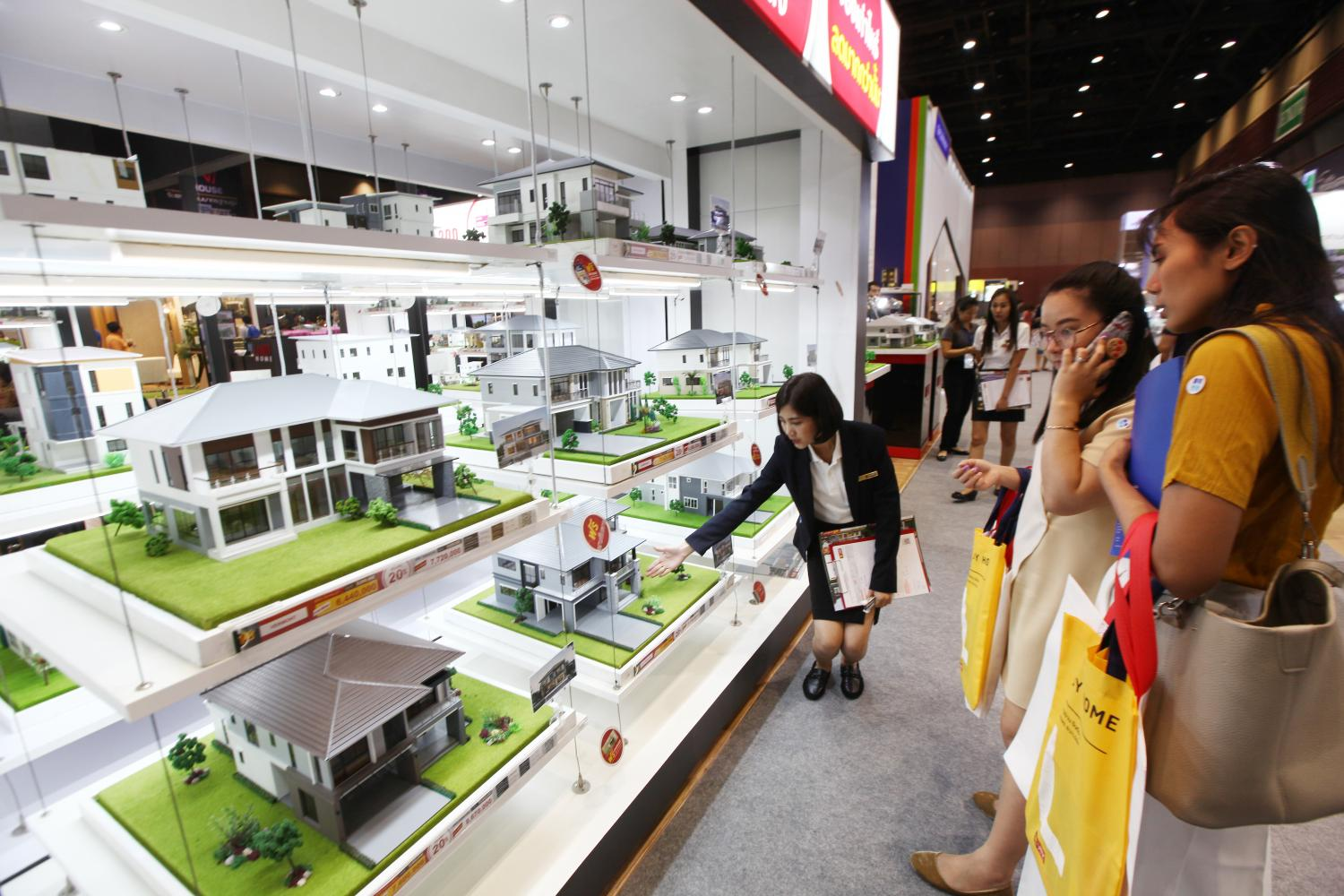 Homebuyers browse model homes at a housing fair. The REIC says the housing market in the third quarter improved from the previous quarter. Phrakrit Juntawong