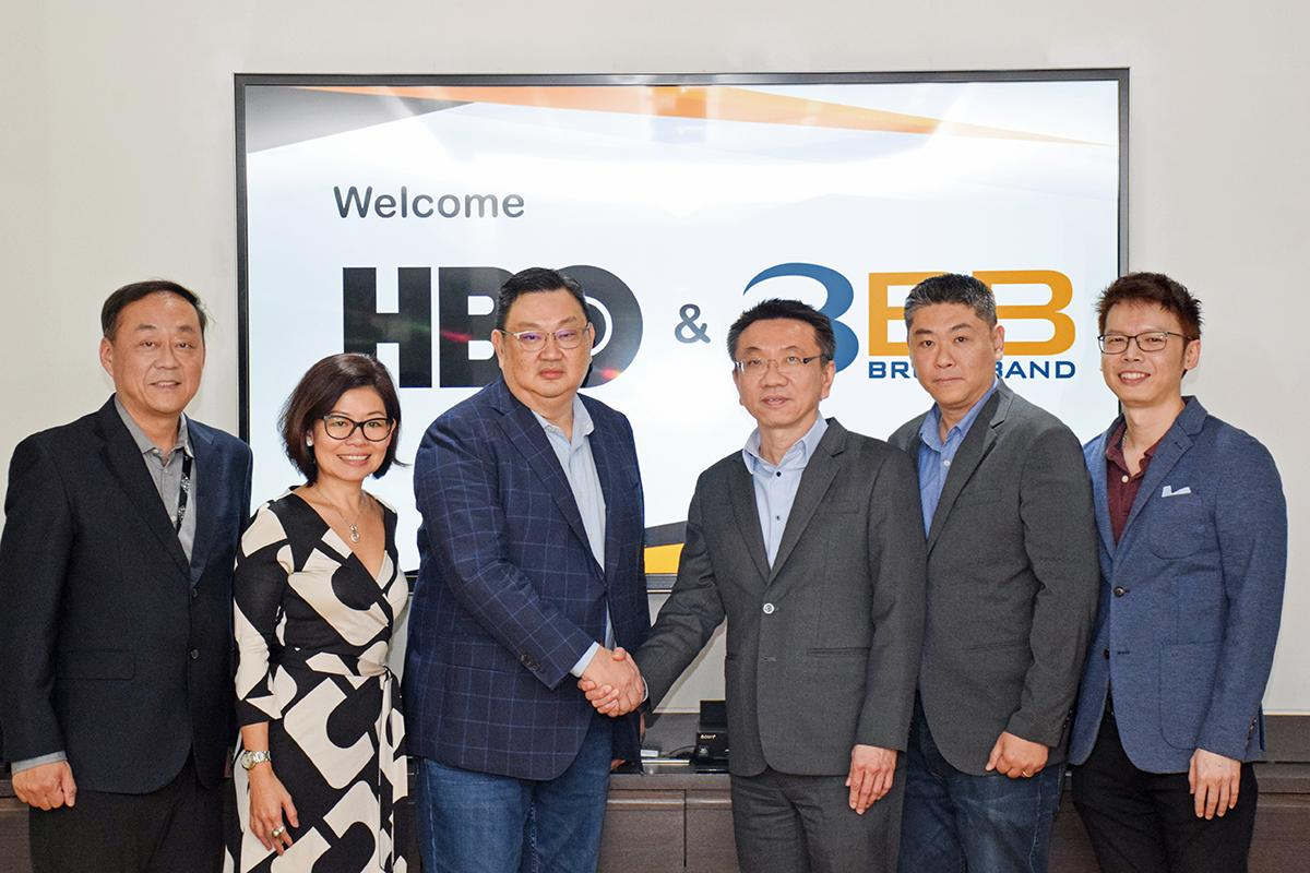 Mr Subhoj, third from right, shakes hands with Ricky Ow, president of WarnerMedia Entertainment Networks Asia, for a collaboration with HBO for content provided on 3BB GIGATV boxes.
