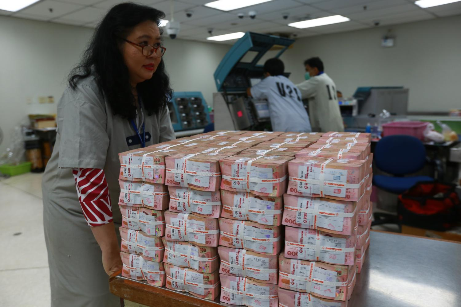 A woman gathers banknotes at Bangkok Bank's headquarters on Silom Road. The baht has appreciated significantly following the US presidential election.(Photo by Somchai Poomlard)