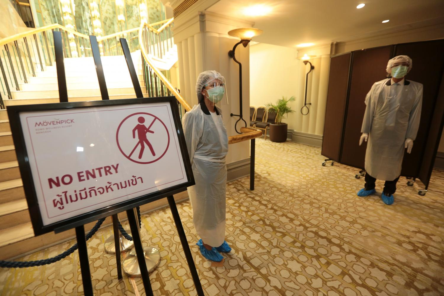 Employees stand ready in protective gear at Movenpick Hotel BDMS Wellness Resort Bangkok, one of the alternative state quarantine facilities for inbound travellers. Chanat Katanyu