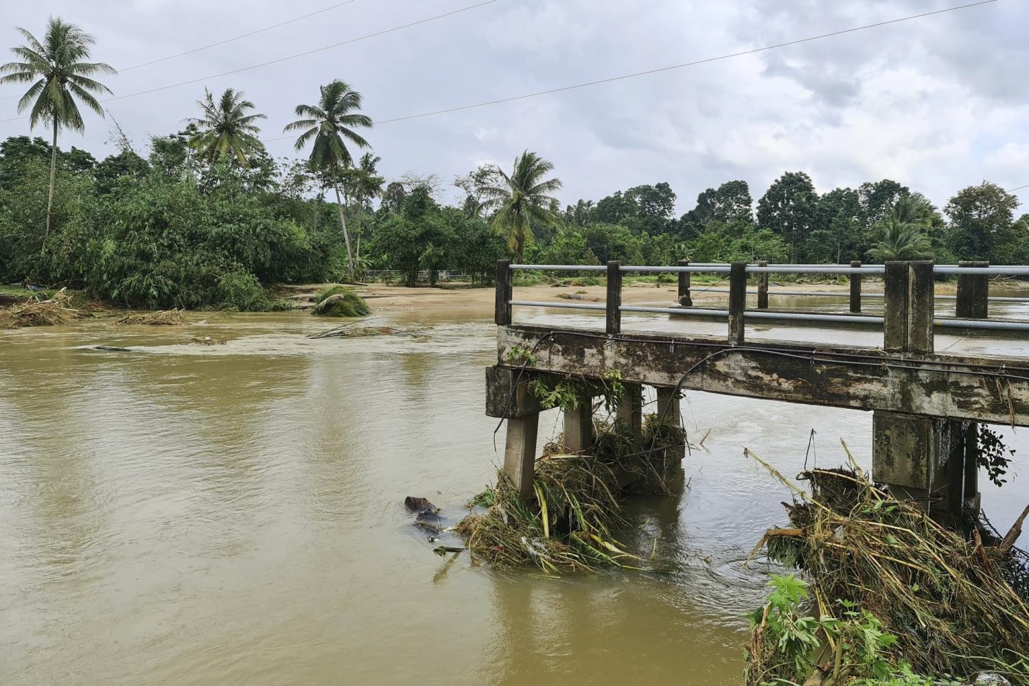 A bridge crossing the Tha Di canal in Lan Saka district, Nakhon Si Thammarat, has collapsed due to major flooding that has ravaged the province since Wednesday. (Photo courtesy of Nakhon Si Thammarat Facebook page)