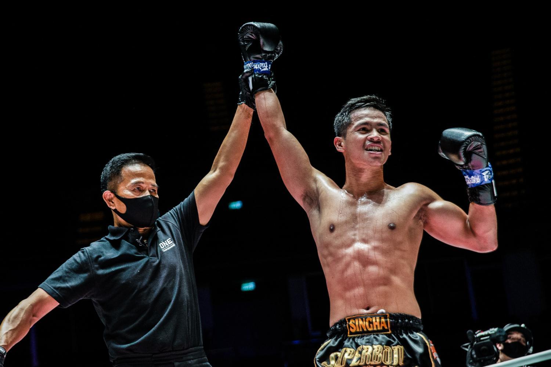 Thai fighter Superbon (right) celebrates a win.