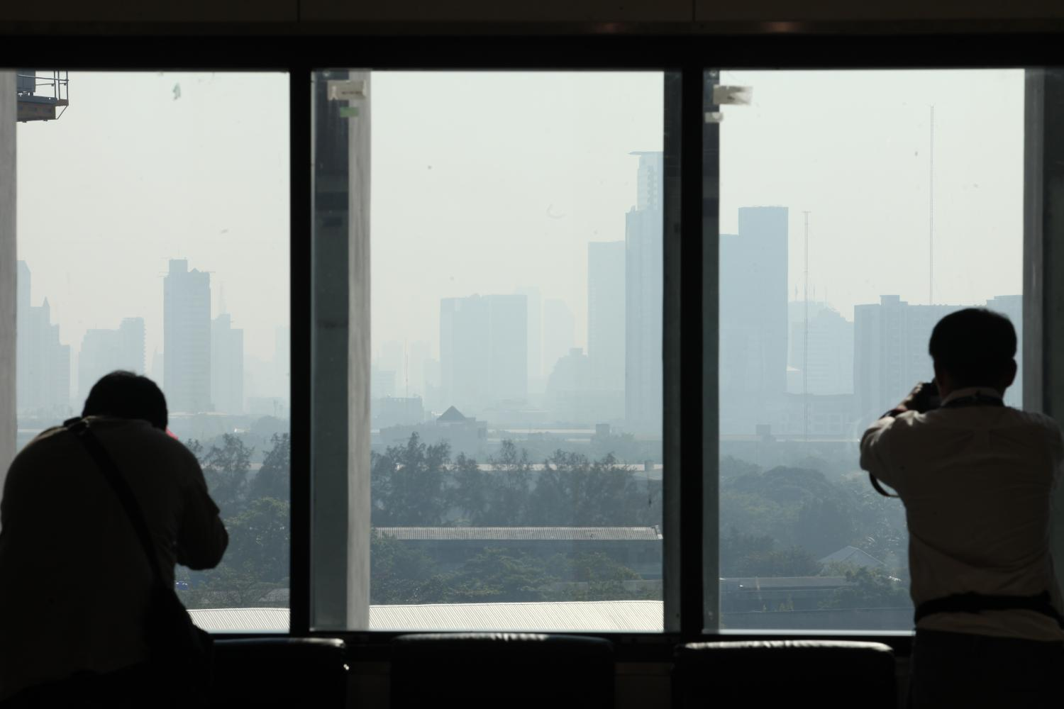 Two photographers take photos of high-rise buildings shrouded in PM2.5 smog from parliament hall on Thursday. (Photo by Apichart Jinakul)