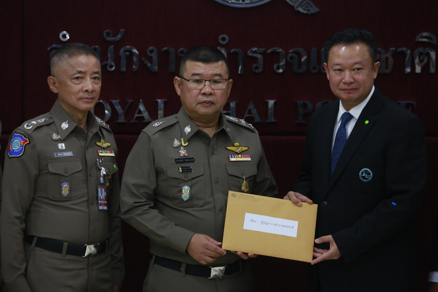 Mr Yuthasak, right, submits a complaint for investigation of unusual transactions in the 'We Travel Together' campaign to the Royal Thai Police. Arnun Chonmahatrakool