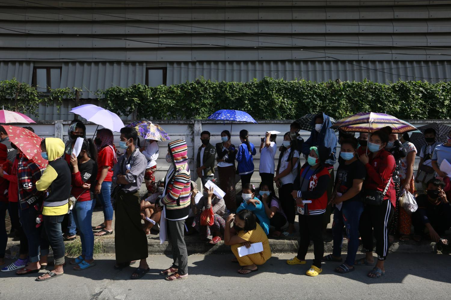 People wait patiently in a queue to receive assistance at a Covid-19 testing centre in Baan Eua Arthorn Tha Chin in Samut Sakhon on Tuesday. (Photo by Arnun Chonmahatrakool)