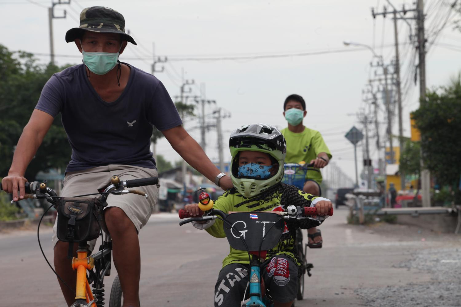 A man takes his son cycling in Bangkok's Bang Khunthian district. People are now wearing masks not only to protect themselves from Covid-19, but also fine dust pollution, which has spiked in parts of Bangkok. (Photo by Apichart Jinakul)