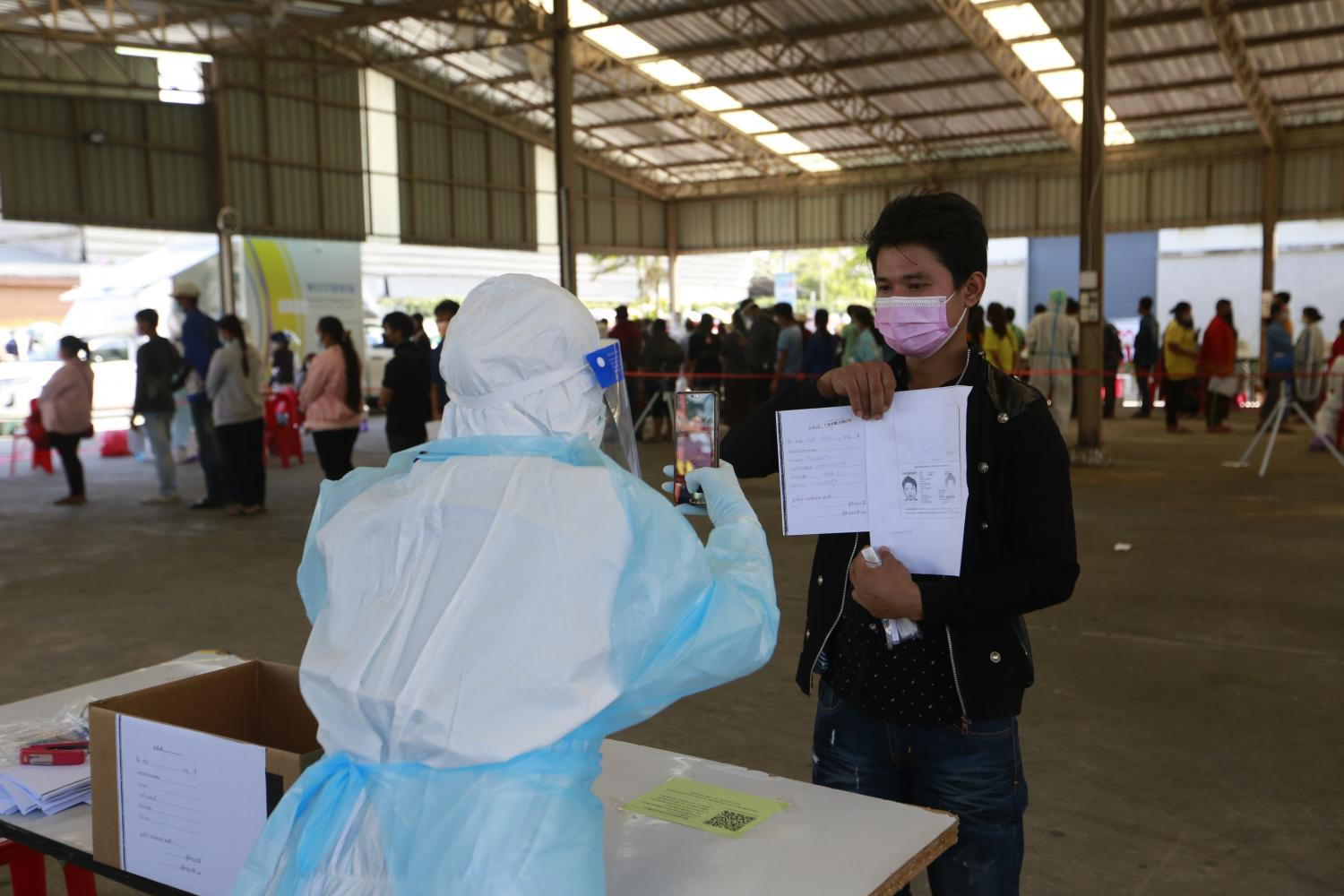 Migrant workers receive assistance on Tuesday at a Covid-19 testing centre in Baan Eua Arthorn Tha Chin in Samut Sakhon. (Photo by Arnun Chonmahatrakool)