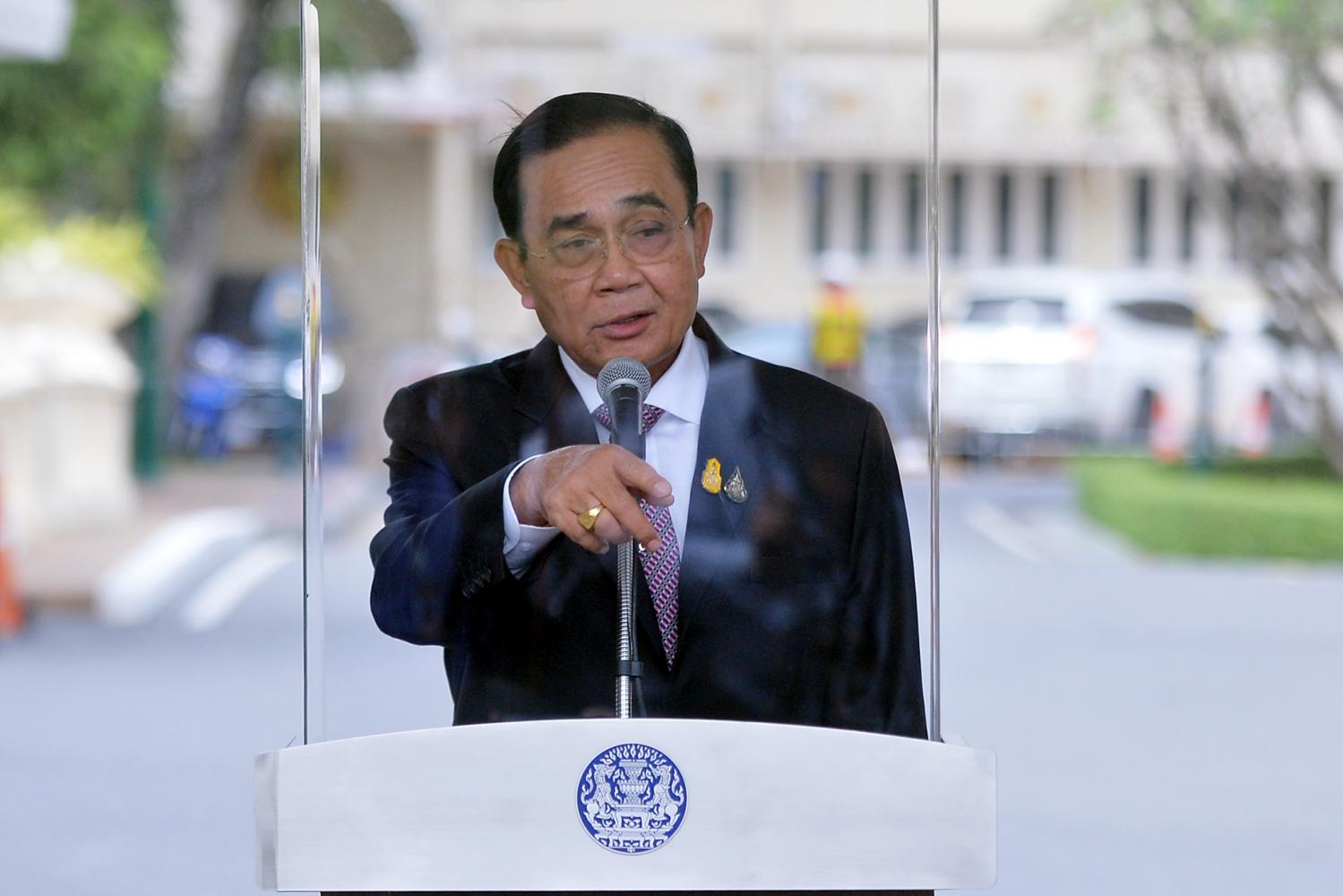 Prime Minister Prayut Chan-o-cha speaks behind a transparent partition during a press conference at Government House on Thursday after officials stepped up disease control measures following the new Covid-19 outbreak. (Government House photo)