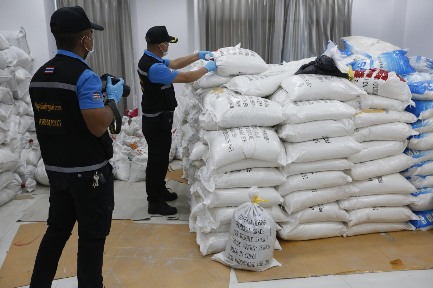 Police officers check sacks at a warehouse in Chachoengsao. The substances turned out to be trisodium phosphate.