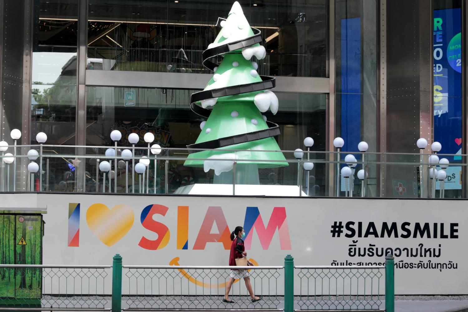A woman walks past a Christmas tree in Siam Square. With Covid-19 infections on the rise, consumer spending across the country is expected to decline during the New Year period.  Chanat Katanyu