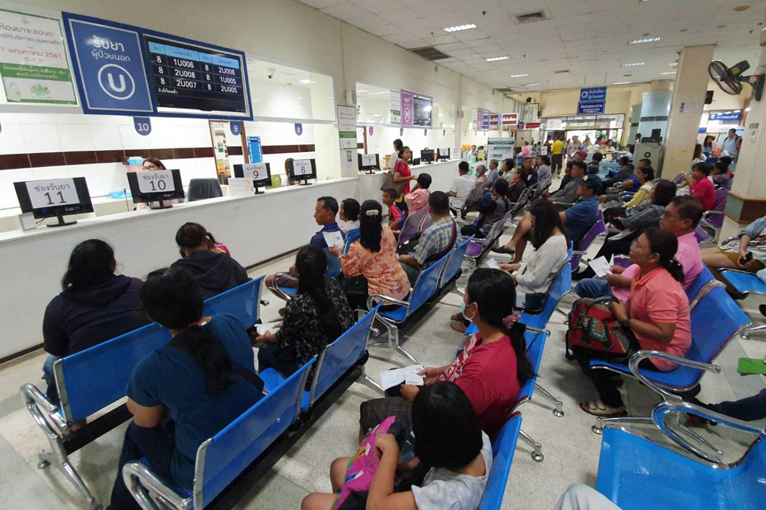 A busy waiting area at Buddhachinaraj Hospital in Phitsanulok on Oct 1. The hospital has since launched a pilot project that allows patients to collect medicine at the chemists near their homes to shorten queues.CHINNAWAT SINGHA
