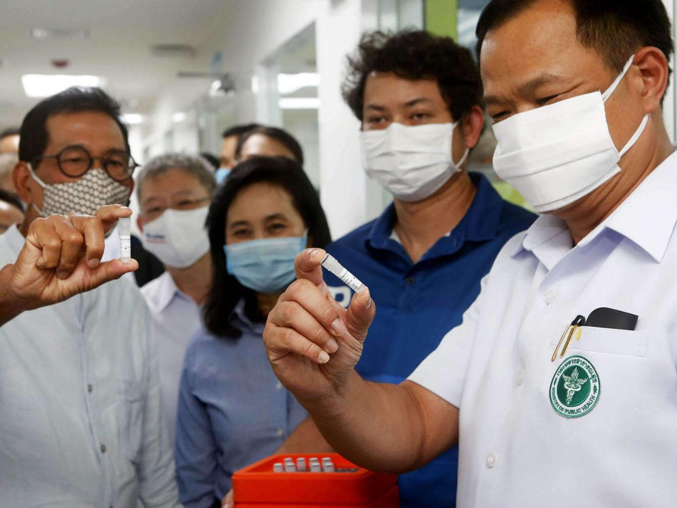 Public Health Minister Anutin Charnvirakul, right, looks at solution samples on June 1 at the Siam Bioscience Group, which produces Covid-19 test kits. Pattarapong Chatpattarasill