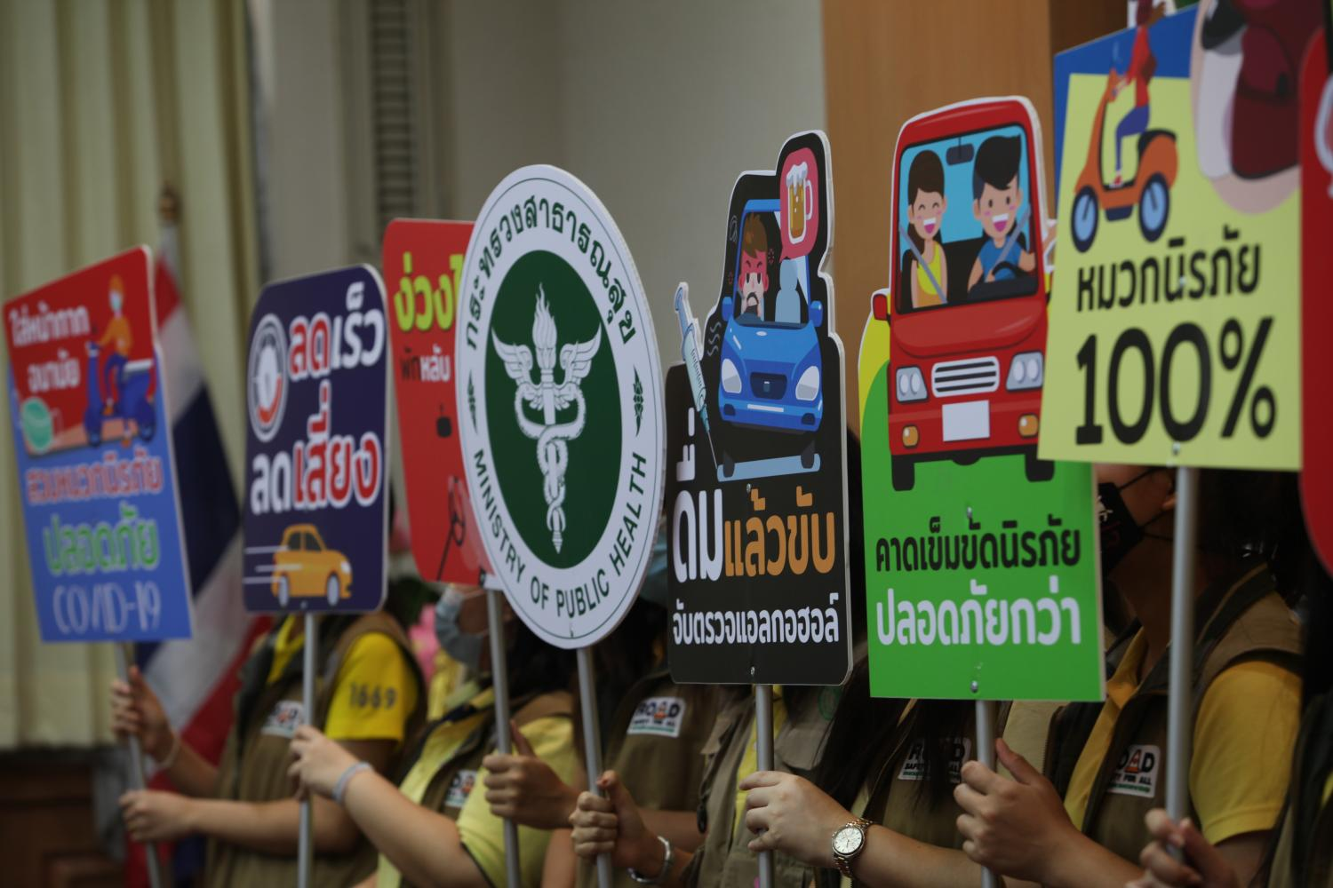 Activists hold up placards encouraging motorists to drive safely during the forthcoming New Year holiday, in a road safety campaign launched by the Public Health Ministry on Monday in Bangkok. Apichart Jinakul