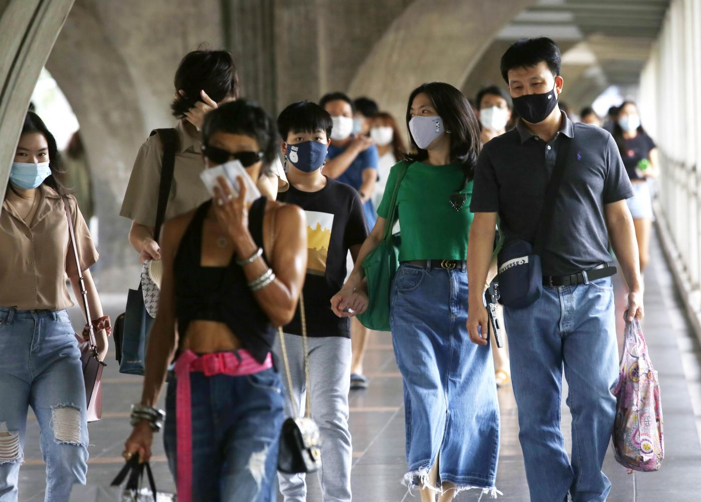 People wear facial masks to protect against Covid-19 while on the skywalk connecting Ratchaprasong intersection and CentralWorld to Siam skytrain station.Apichit Jinakul