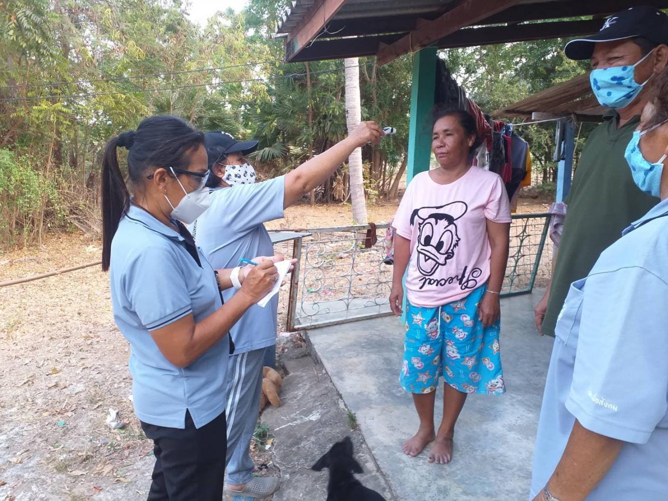 Village health volunteers take the body temperature of a resident during a door-to-door visit in Prachuap Khiri Khan in April.Nopphanat Subhakul
