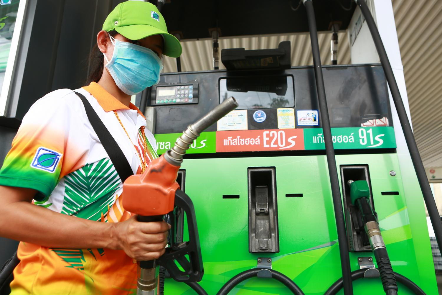 A worker wears a protective mask at a Bangchak petrol station. Officials want E20, a mix of 20% ethanol and 80% unleaded gasoline 95, to gradually replace gasohol 91.Somchai Poomlard