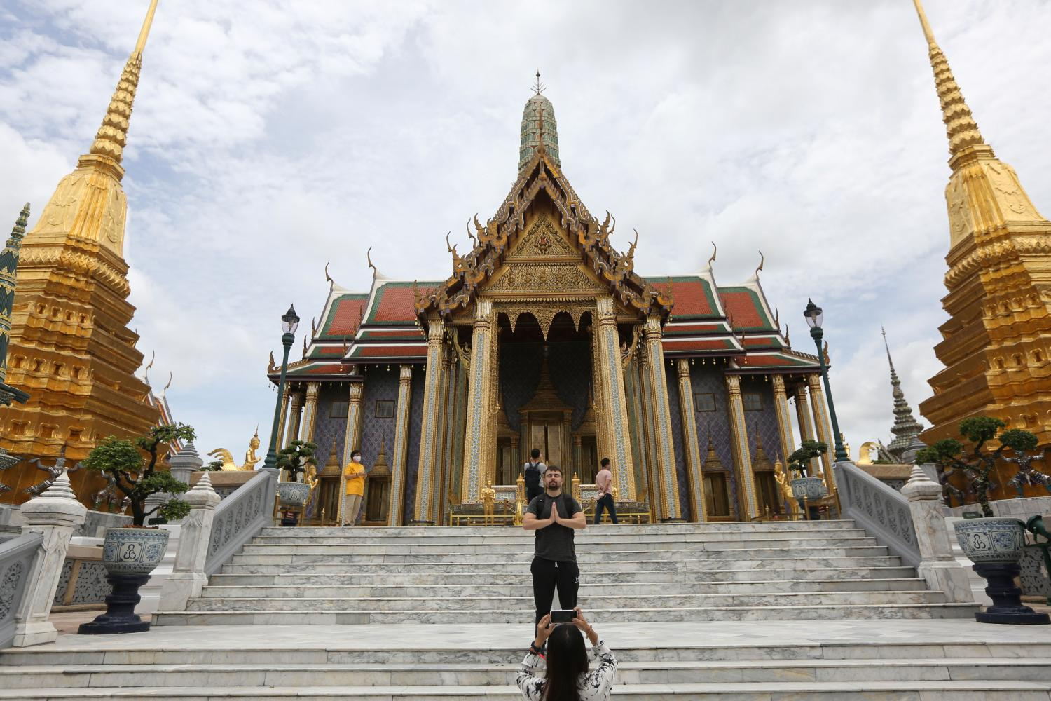 A visitor poses for a photo outside Prasat Phra Dhepbidorn or the Royal Pantheon inside the Grand Palace which reopened to the public in May after two months of closure forced by the pandemic.Wichan Charoenkiatpakul