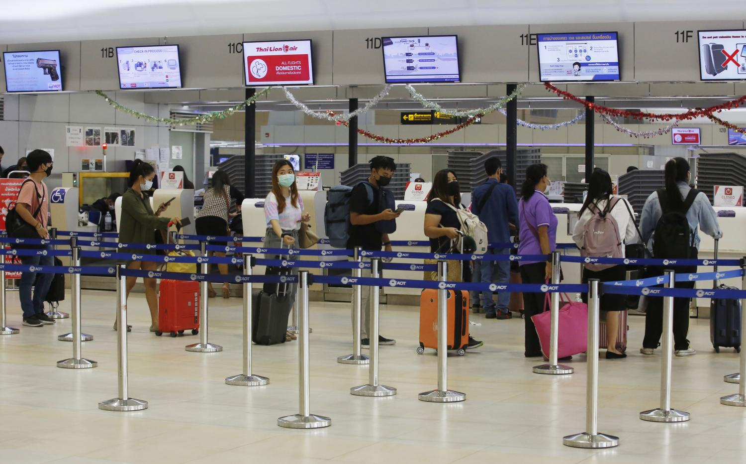 Tourists queue for check-in at Don Mueang airport.