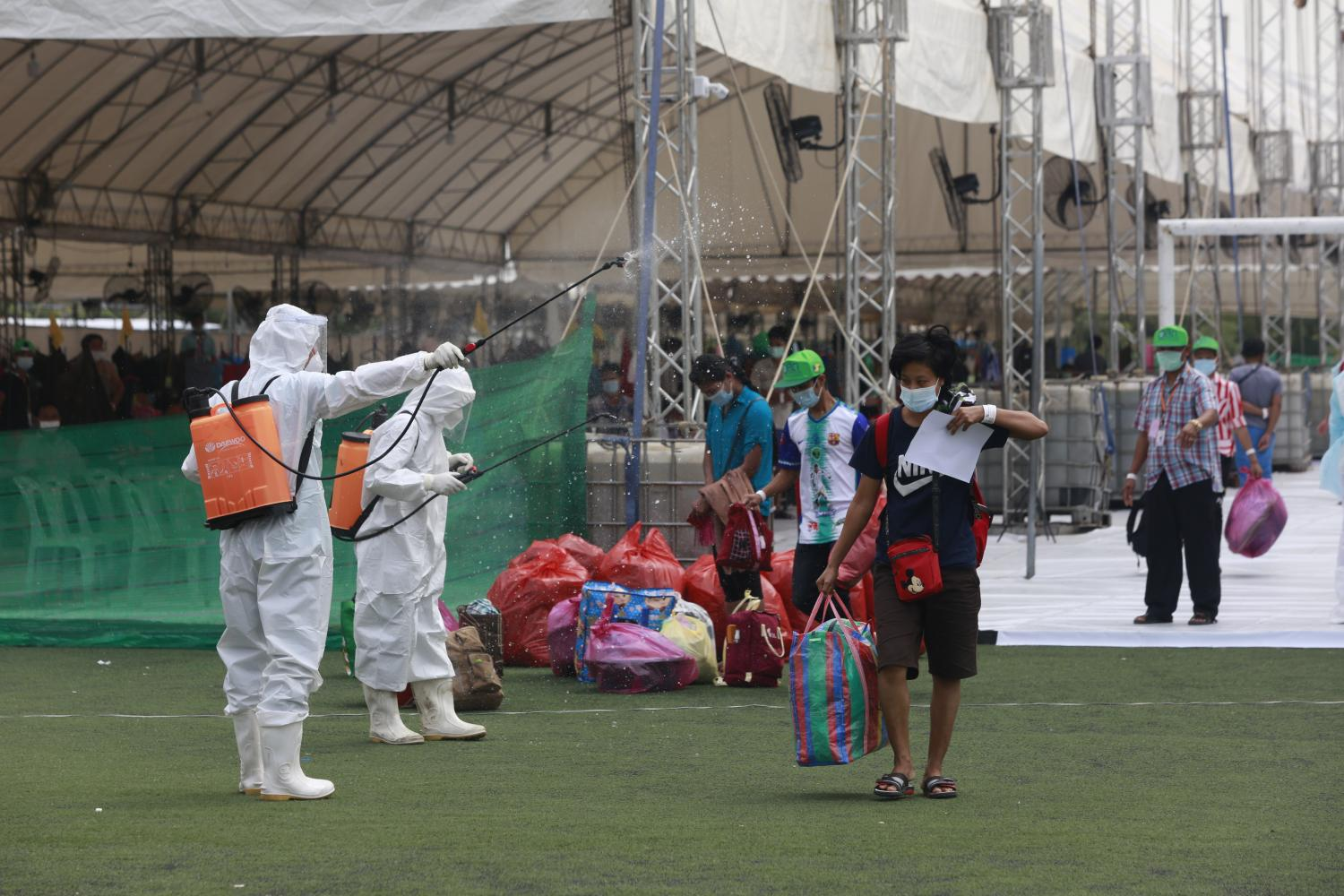 Migrant workers get sprayed with disinfectant as they leave the Covid-19 field hospital at Samut Sakhon's provincial stadium, after completing their quarantine period. (Photo by Arnun Chonmahatrakool)