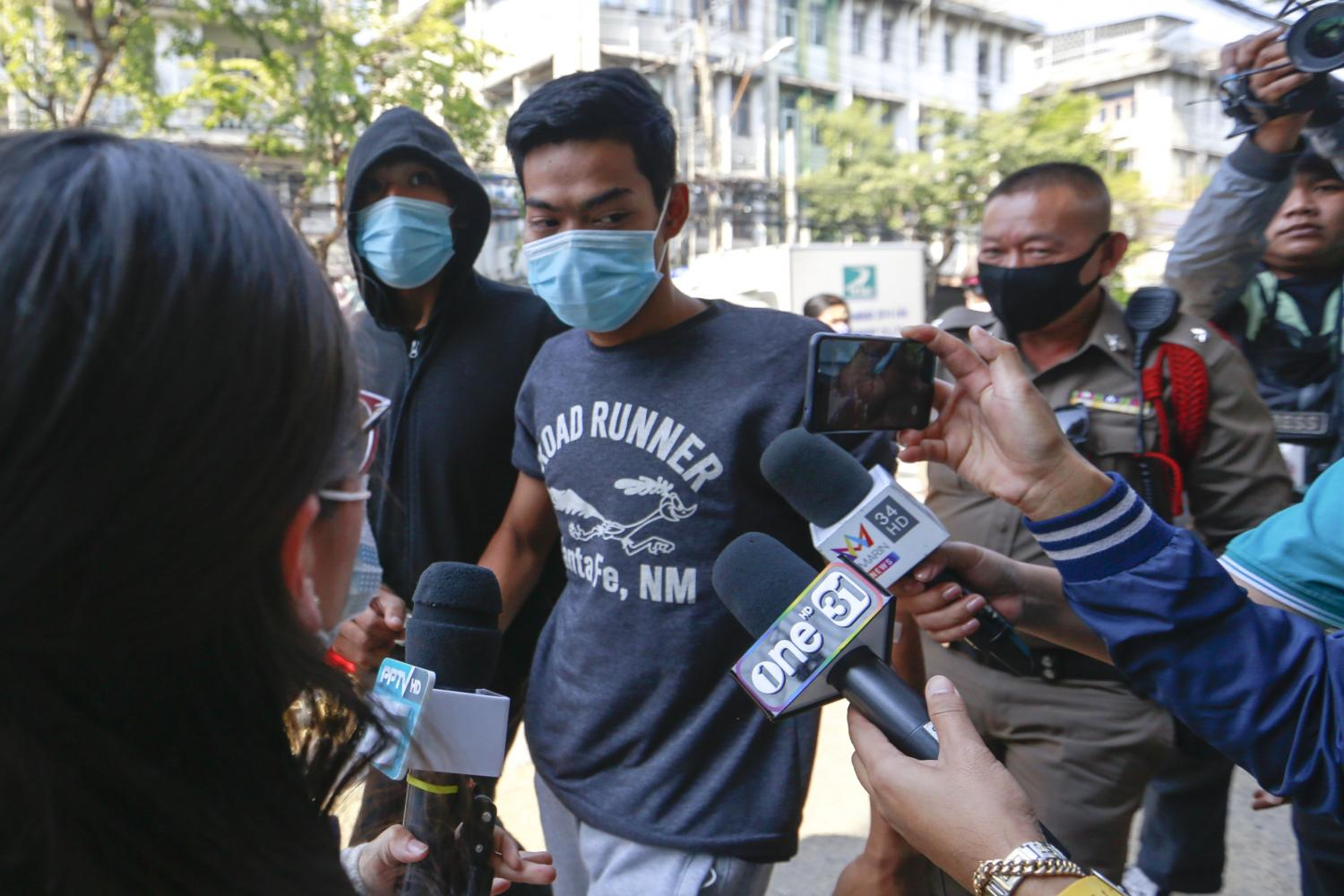 Chatree Srisombat, 19, (in the 'Runner' shirt) and Noppakao Obthom, 26, (in the hooded jacket) are escorted to Wat Phraya Krai police station on Wednesday. Mr Chatree was charged with selling the fatal 'k-powdered milk' blend and Mr Noppakao with possessing the drug. (Photo by Arnun Chonmahatrakool)