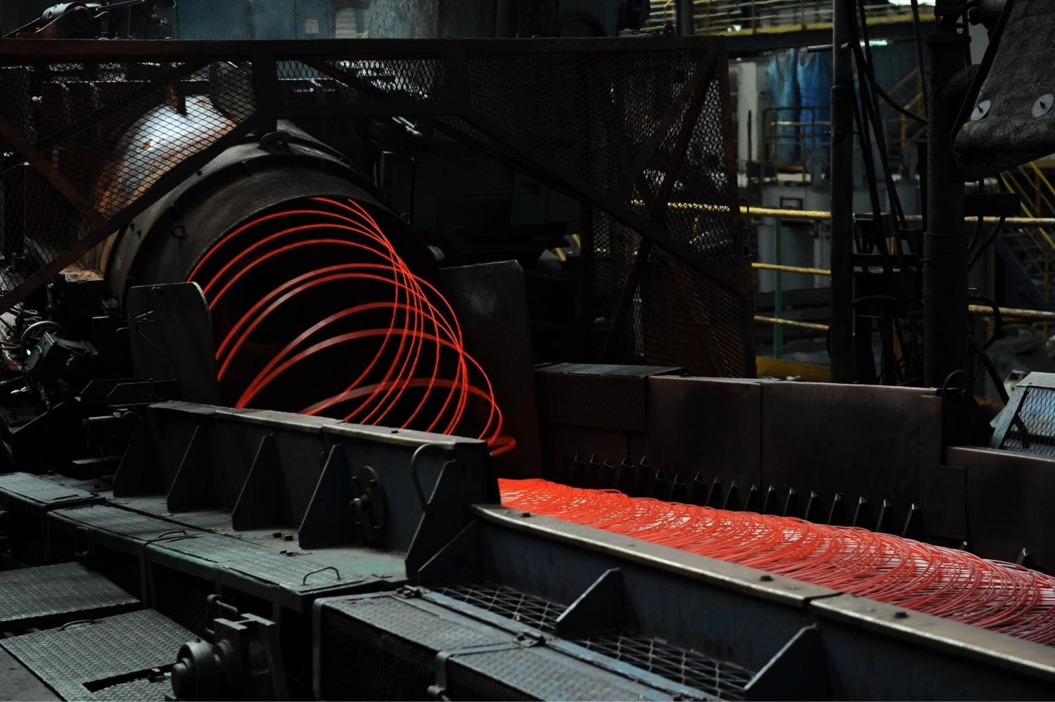 Hot-rolling steel rods being churned out at the Kobelco Millcon Steel factory in Rayong.