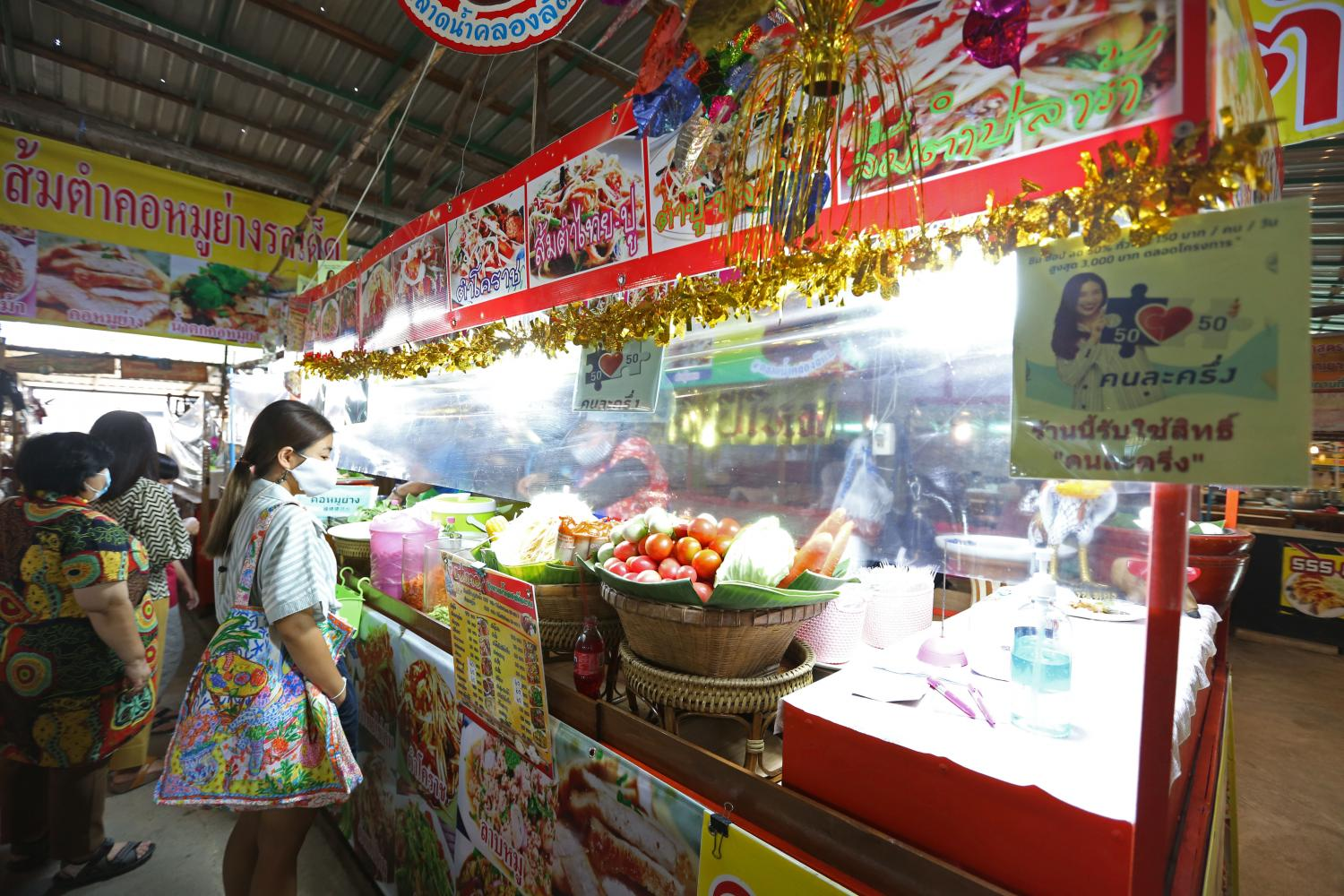 A food stall at Khlong Lat Mayom Floating Market offers co-payment.