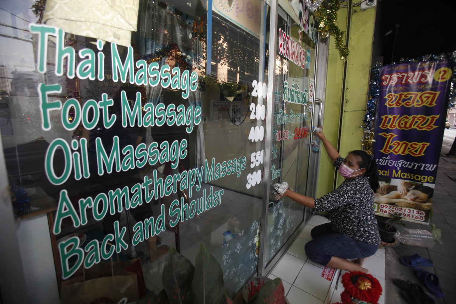 Ready for business: A woman cleans the front window of her traditional Thai massage shop in the Inthamara area of Bangkok as the business reopens.