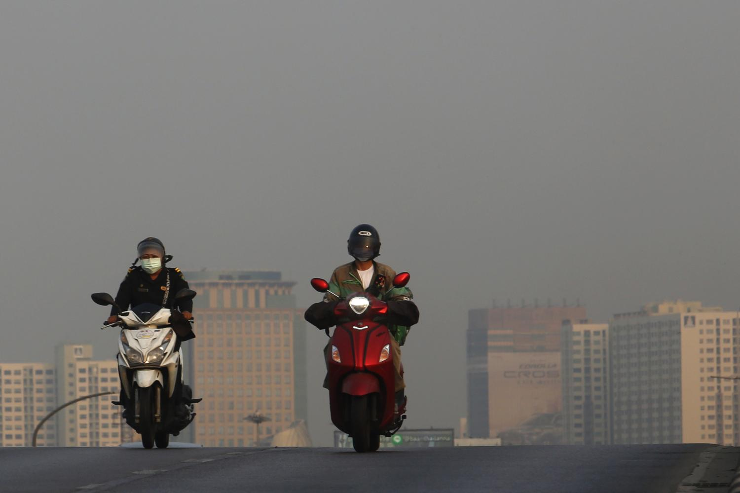 Motorists brave the haze in Bangkok yesterday. Similar conditions were reported in Nakhon Ratchasima, where micro-dust levels have exceeded the safe level for five days straight.(Photo by Wichan Charoenkiatpakul)