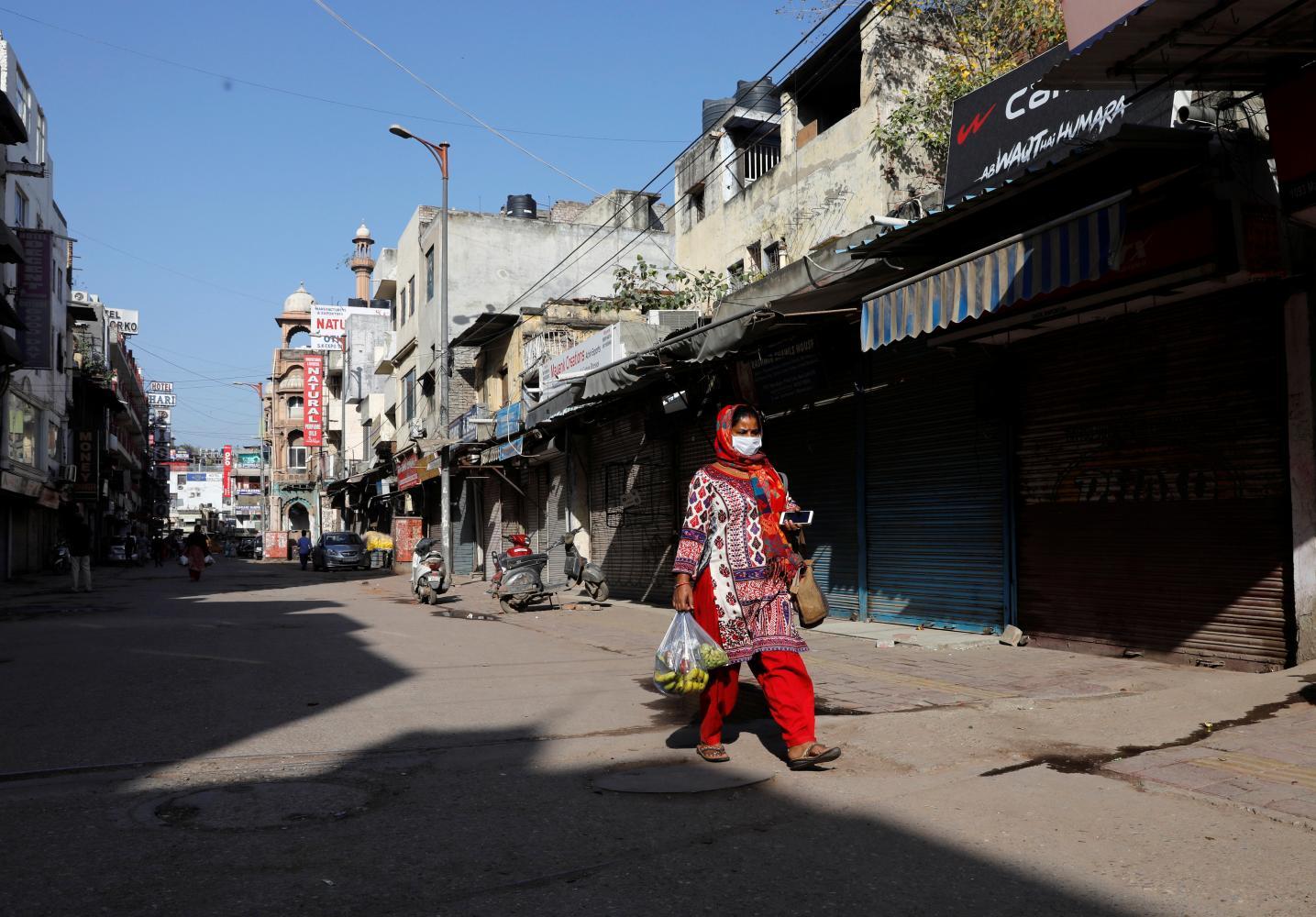 A woman walks along a near-empty street in New Delhi during a lockdown in March. Photo: ADNAN ABIDI/REUTERS