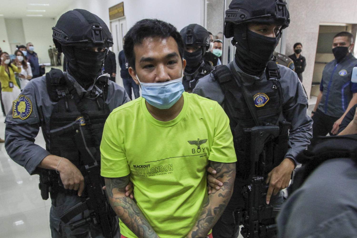 Siapo Po-arnon is escorted by armed police after being arrested at his house in Bangkok on Thursday. Pattarapong Chatpattarasill