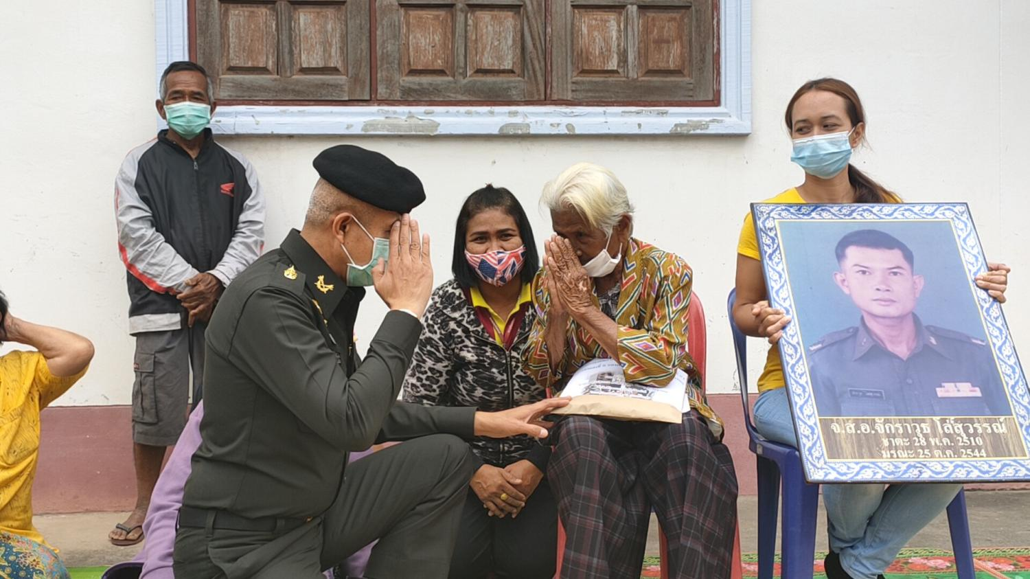 GRATITUDE: Buan Losuwan, 89, right, is greeted by a senior army officer who presented her with money donated by fellow military personnel to help her repay debt to the state.