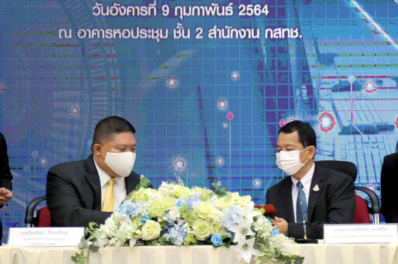 Acting secretary-general of NBTC Trairat Viriyasirikul, left, and Mr Sirirerk sign the MoU yesterday.