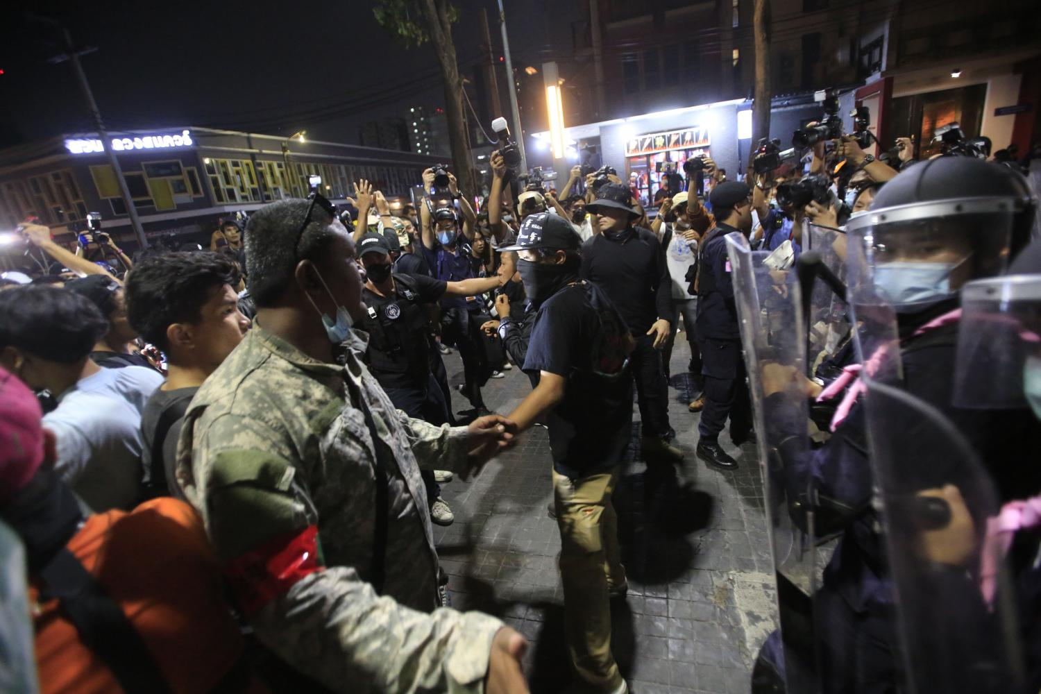 Demonstrators confront police in riot gear Wednesday night at Suan Luang Square, where they gathered to demand the release of 10 protest leaders detained at nearby Pathumwan police station.(Photo by Pornprom Satrabhaya)