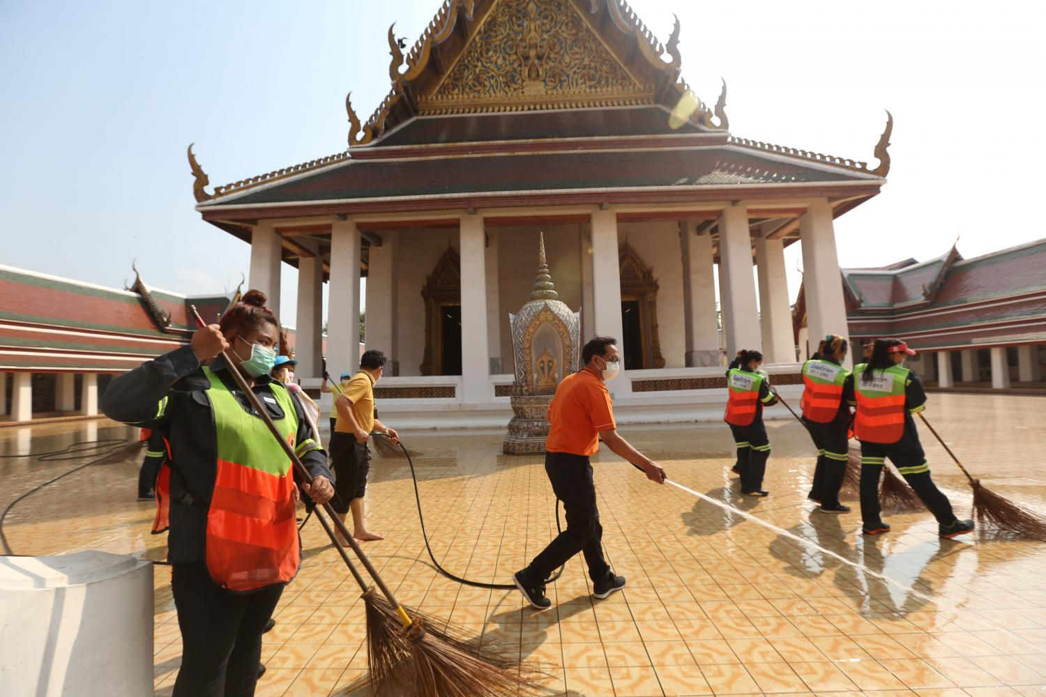 Officials spray water as part of a big cleaning effort at Wat Saket to prevent the spread of Covid-19 on Sunday. Anti-government protesters on Friday called a rally including plans to string a red cloth banner at the temple's Golden Mount, but had to change the plan and hold it on Saturday instead after the temple announced its big clean-up.Varuth Hirunyatheb