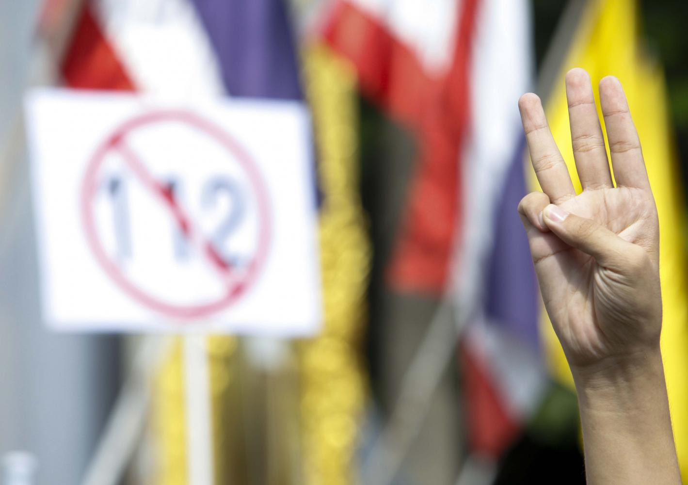 An activist flashes a three-finger sign as he joins a demonstration calling for monarchy reform and charter amendments in Nonthaburi in December last year.Pattarapong Chatpattarasill