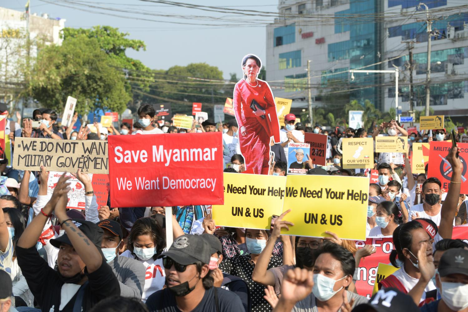 Demonstrators hold placards and a cutout with the image of Aung San Suu Kyi during a protest against the military coup in Yangon, Myanmar, yesterday. REUTERS