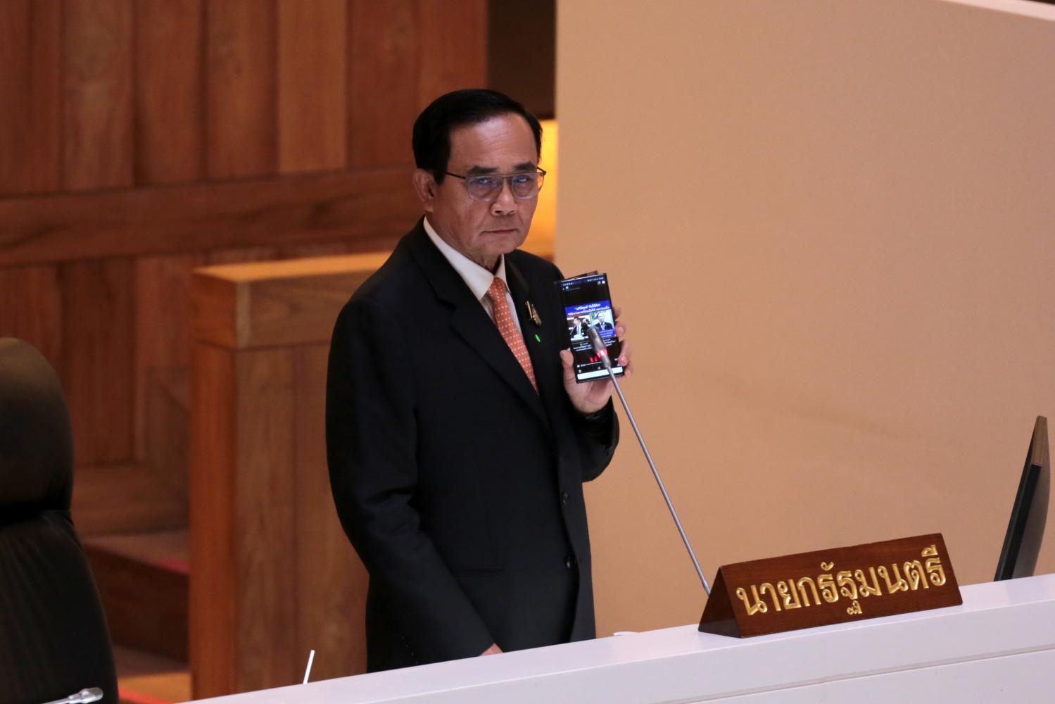 Prime Minister Prayut Chan-o-cha plays a video clip on his phone to counter a claim made against him by Pol Gen Sereepisuth Temeeyaves, leader of Seri Ruam Thai Party.(Photos by Chanat Katanyu)