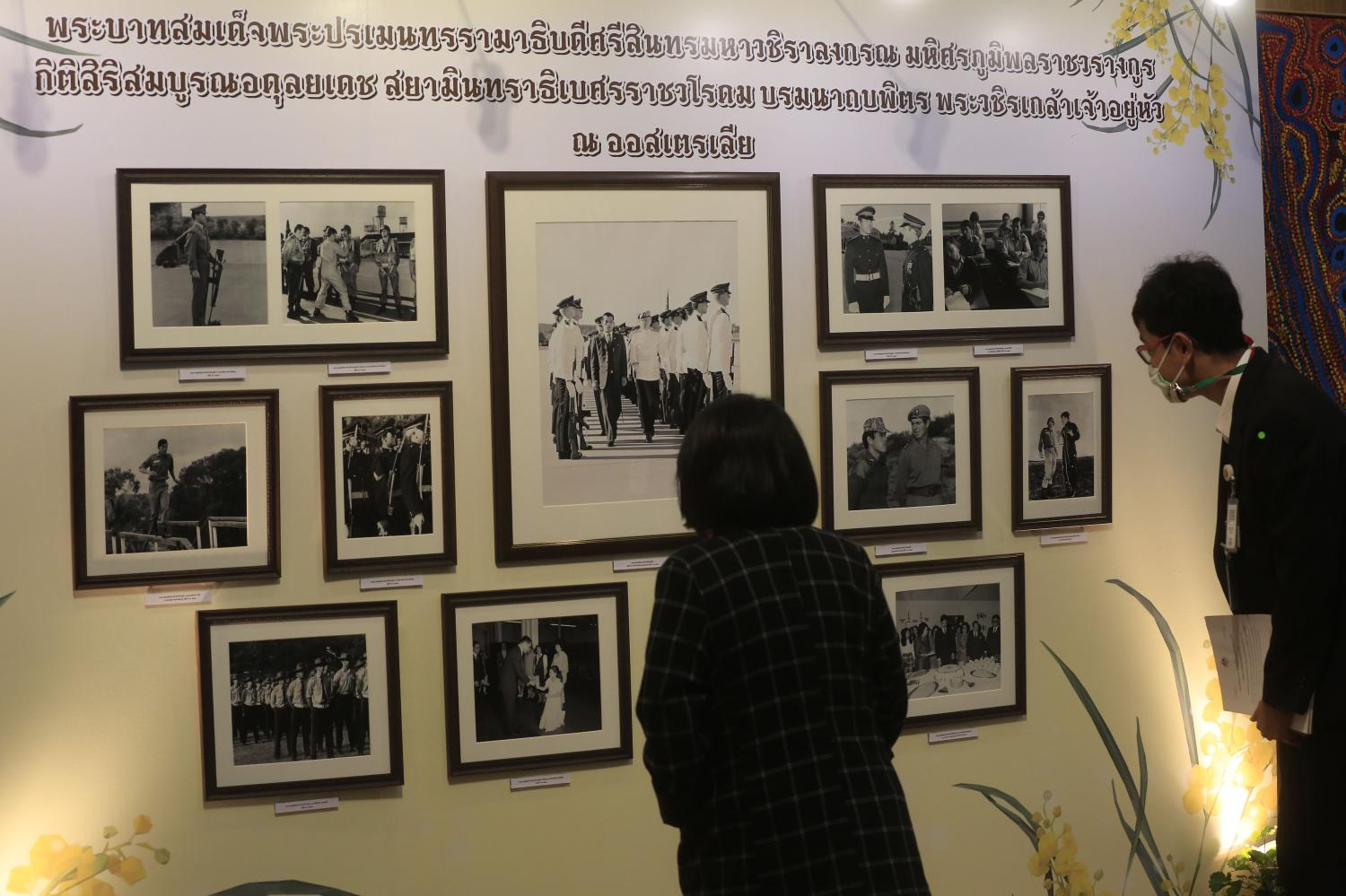 Visitors look closely at framed photos of His Majesty at the Australian embassy. A new documentary commemorating the King's time in Australia produced by the embassy will be aired on TV Pool until Thursday.(Photo by Pornprom Satrabhaya)