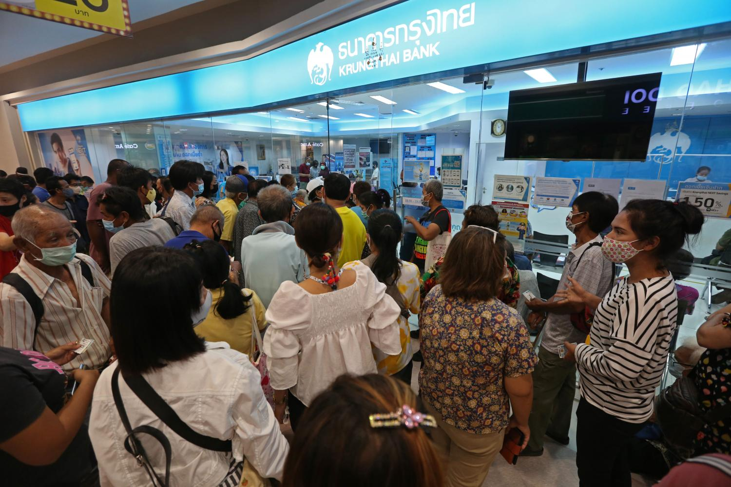 Hundreds of people wait at a Krungthai Bank branch in a city superstore to register for financial aid under the Rao Chana scheme.(Photo by Varuth Hirunyatheb)