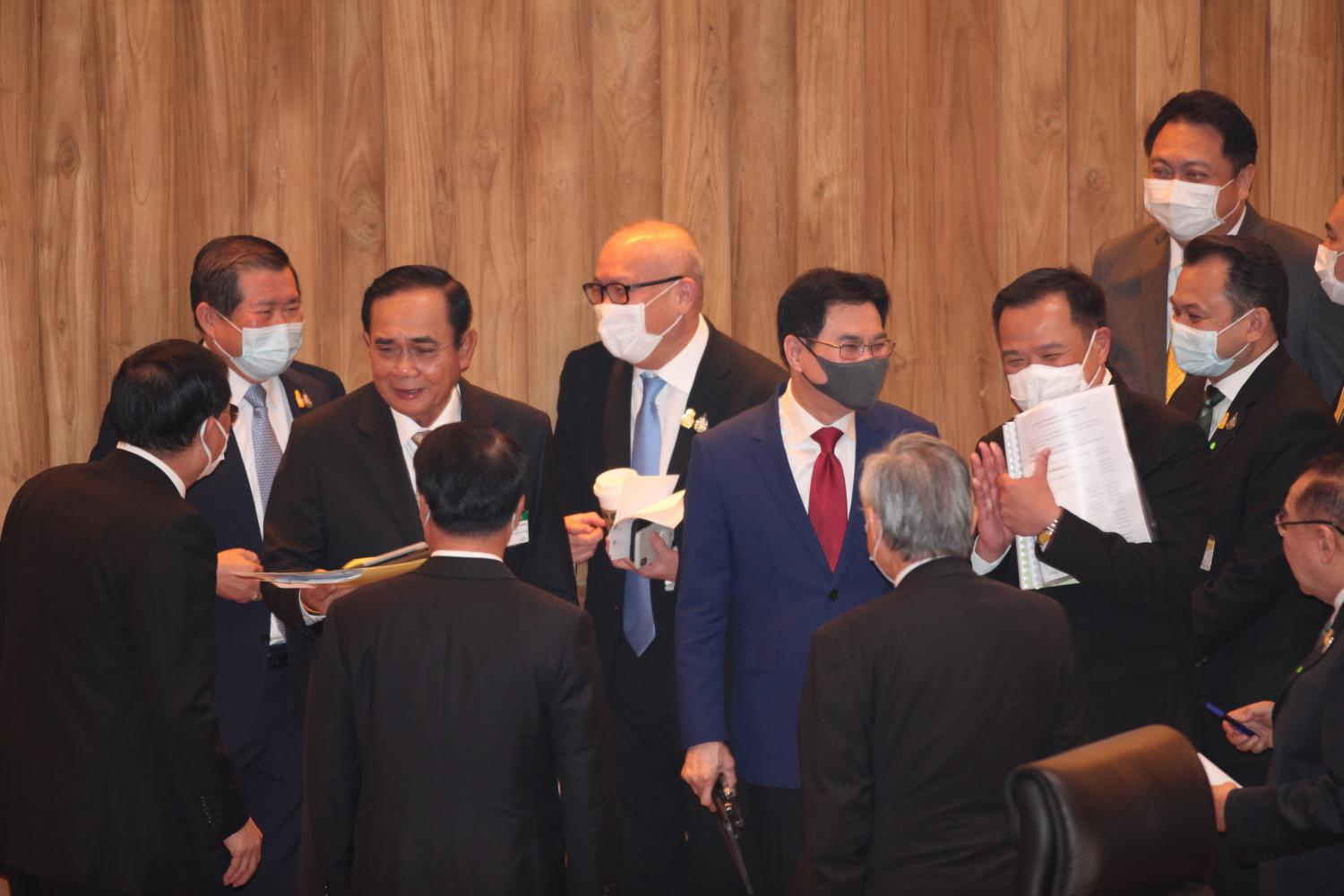 Prime Minister Prayut Chan-o-cha and other cabinet ministers targeted for the censure grilling greet each other in the chamber after they survived the no-confidence motion yesterday. The vote followed a four-day debate which ended on Friday.