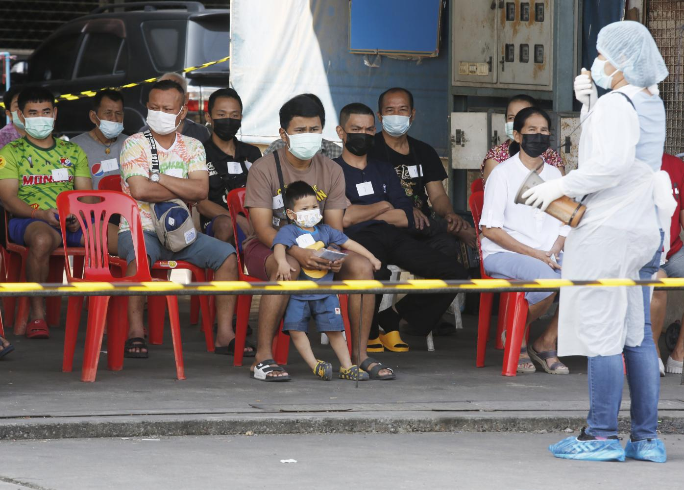 attention, please: A health official explains procedures for Covid-19 testing at Pornpat market on Rangsit-Pathum Thani Road in Pathum Thani yesterday. Shops were closed for cleaning and people connected to the market were tested after infections were detected there.