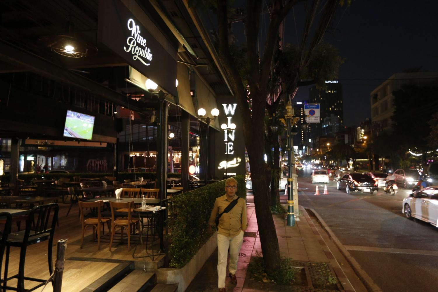 A man walks past a pub in Bangkok's Sukhumvit Soi 55, an area in Thong Lor, last night. Restaurants and entertainment venues in orange zones, including Bangkok, are allowed to serve alcohol until 11pm from March 1.Wichan Charoenkiatpakul