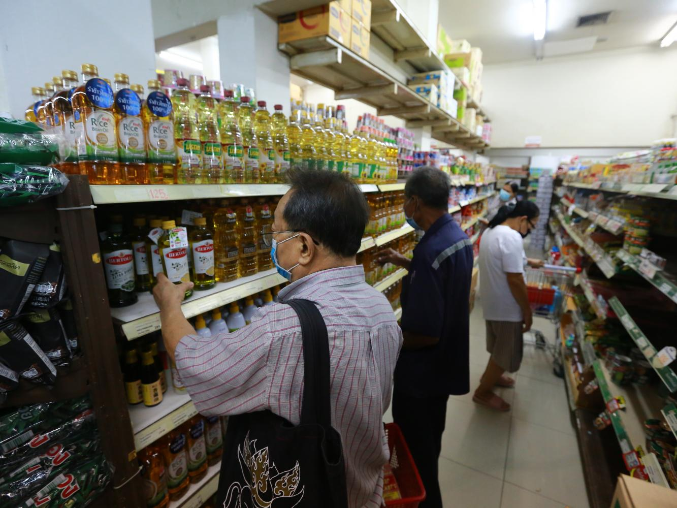 Customers browse vegetable oil products at a store taking part in the 'We Win' scheme in Samut Prakan.Somchai Poomlard