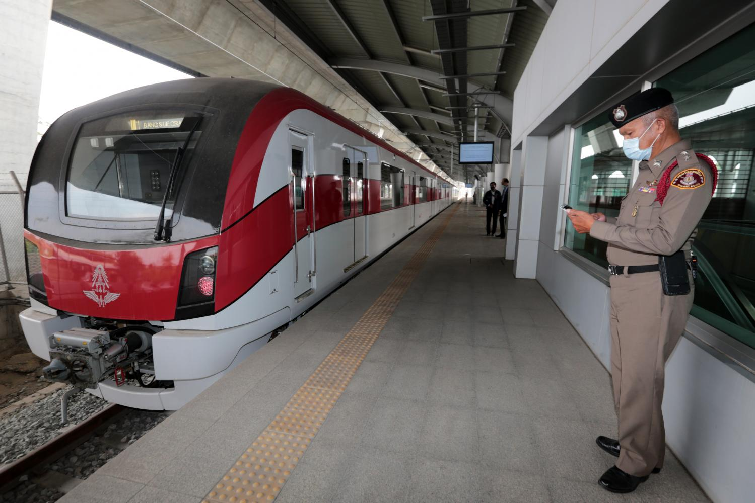 A policeman stands near a Red Line train on Tuesday during a visit by the transport minister. (Photo by Chanat Katanyu)