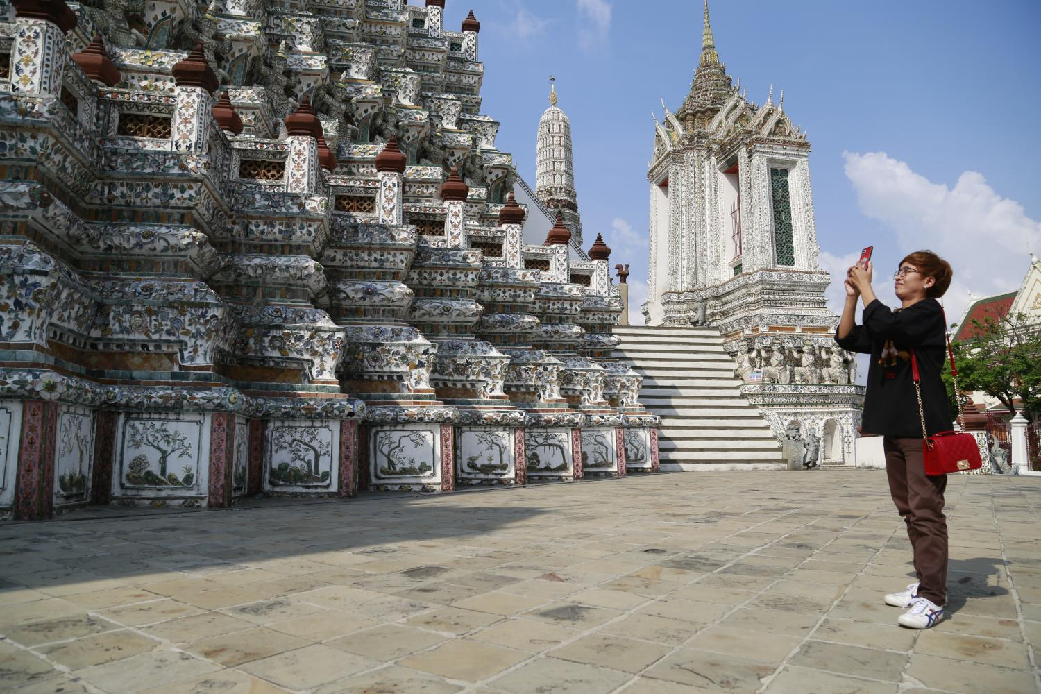 A tourist takes a picture at Wat Arun Ratchawararam Ratchaworamahawihan or Wat Arun which reopened to the public on Feb 15, 2021.(Photo by Arnun Chonmahatrakool)
