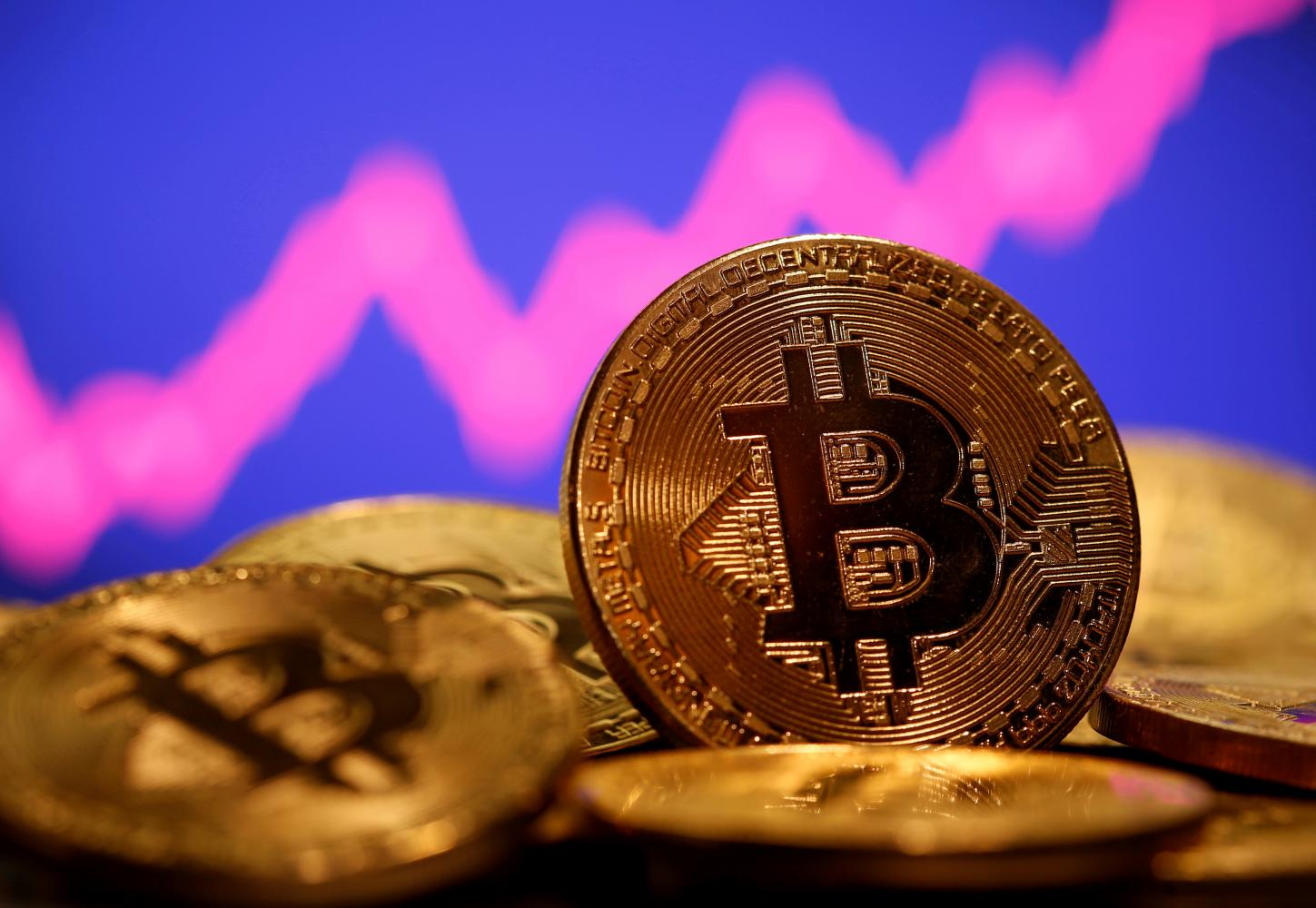 A representation of virtual currency bitcoin is seen in front of a stock graph in this illustration. (Photo: Reuters)