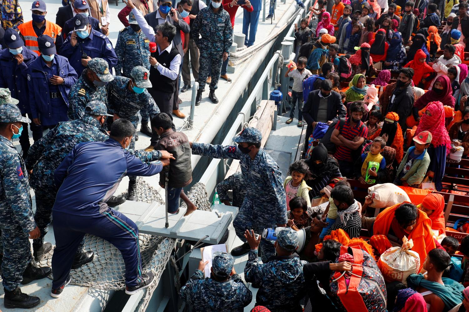 Bangladesh naval personnel help a disabled Rohingya refugee child get off a navy vessel as they arrive at Bhasan Char Island in Noakhali district, Bangladesh, in this 2020 file photo. (Reuters photo)