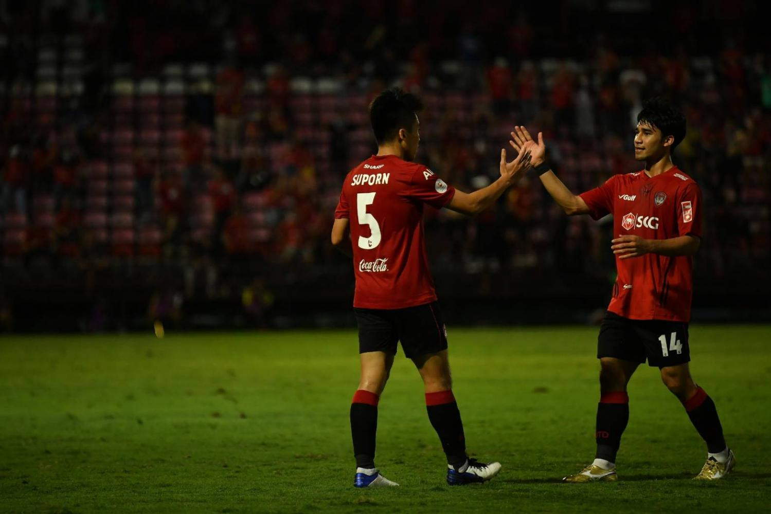 The Kirins' saviour: Muang Thong's Suporn Pinakatapho (left) celebrates his equaliser against Buriram United with teammate Chatmongkol Thongkiri.